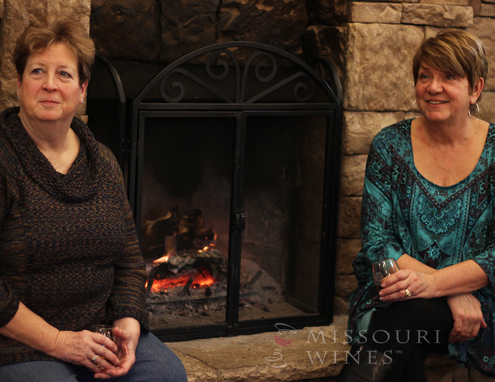 Winter Friendly Missouri Wineries: Two MO wine fans enjoying the warmth of the fireplace and the atmosphere at Keltoi Vineyard.