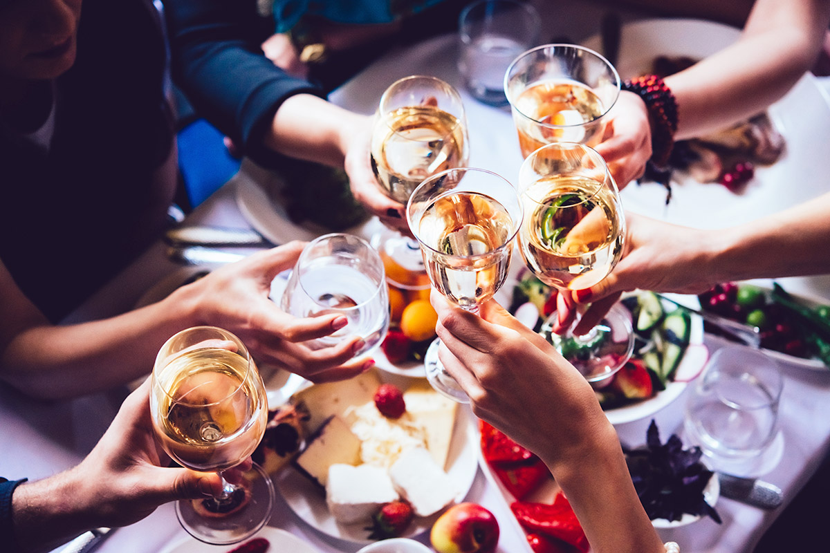 Cheers to Toasting Traditions- Group of friends gathering over a table full of food, toasting