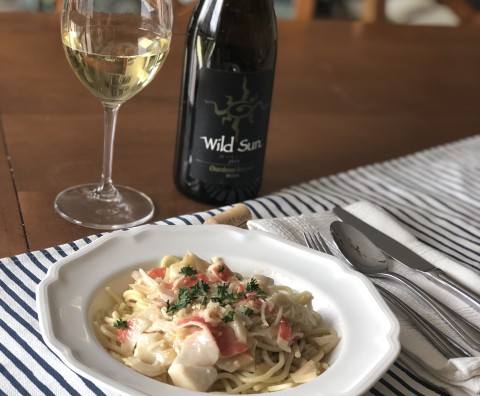 Lemon Butter Seafood Pasta plated with white wine and wine bottle