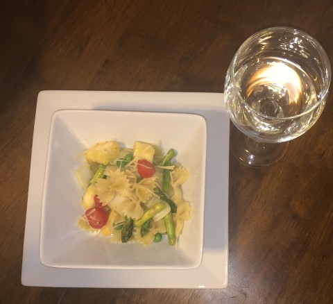 bowl of pasta primavera and glass of Vidal Blanc