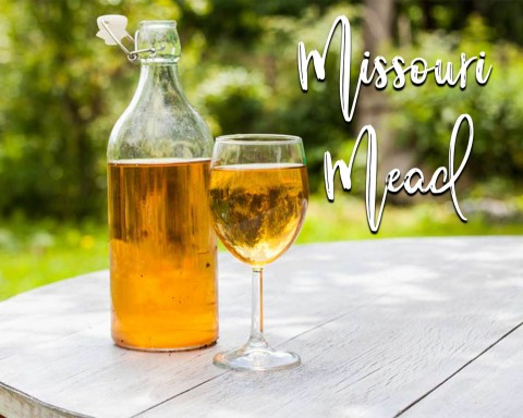 Picture of mead wine in a jar and a glass sitting on picnic table outdoors
