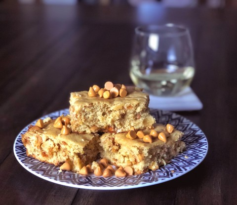 butterscotch blondies stacked on blue and white plates with a glass of chardonel in the background.